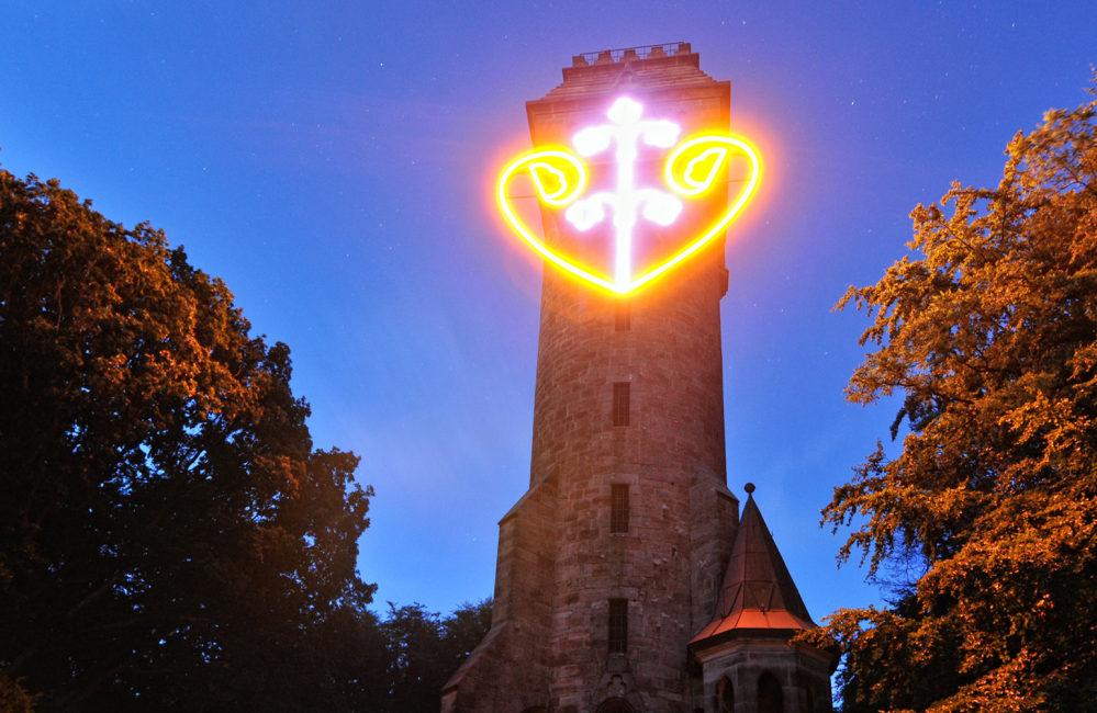 Kaiser-Wilhelm-Turm bei Nacht mit leuchtendem Herzen. Bäume rechts und links.