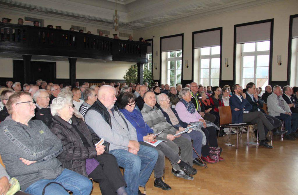 Im Rathaussaal sitzen interessierte Zuhörer, überwiegen 50 Jahre und älter. Die Stühle im Saal sind besetzt, ebenso die Empore. Bürgermeister Thiemig sitzt in der ersten Reihe.