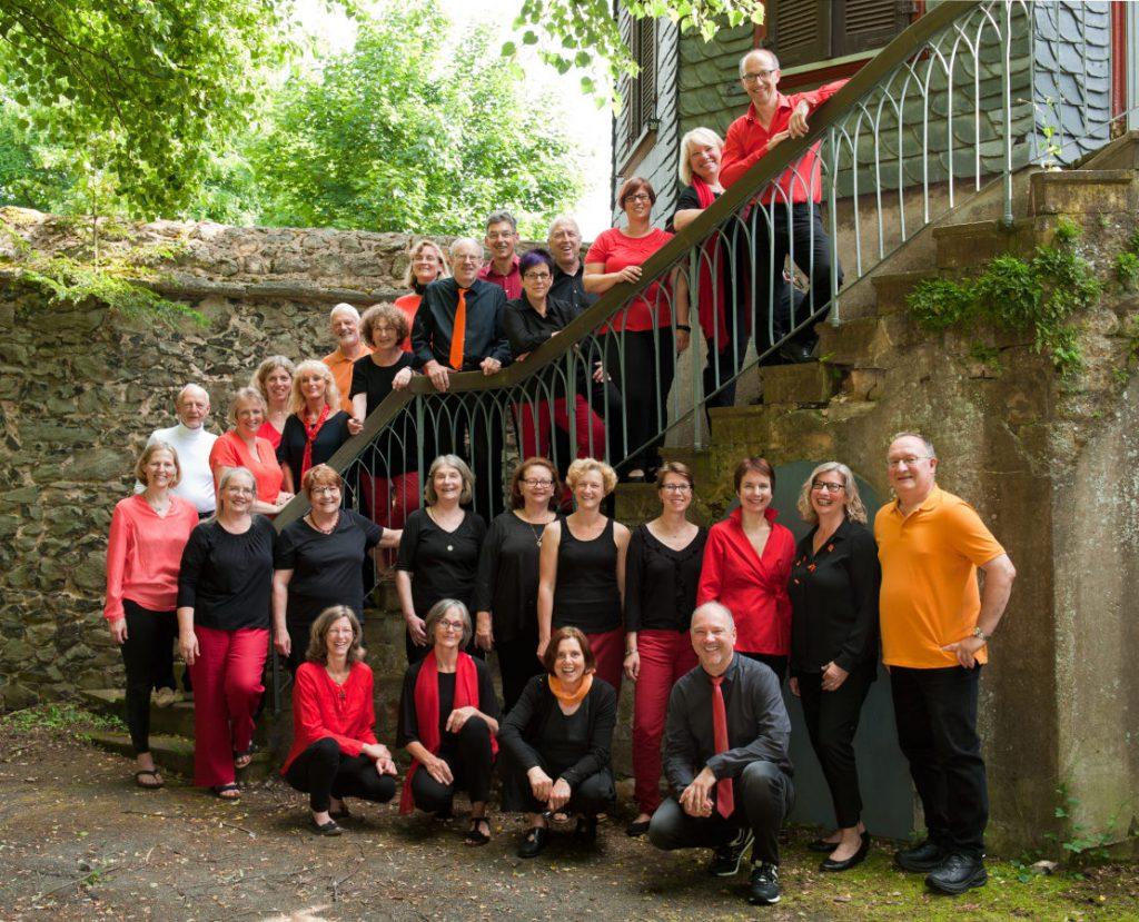 28 Chormitglieder stehen auf einer Treppe, beziehungsweise stehen oder hocken davor. Alle in Schwarz und Rottönen gekleidet.