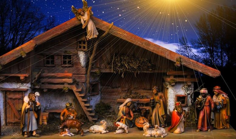 Eine Holzkrippe mit der Heiligen Familie, samt Jesus-Kind, Hirten und Weisen, ein Engel schwebt darüber. Ein heller Schein geht vom Himmel aus auf die Szenerie. Der Heiland ist geboren.