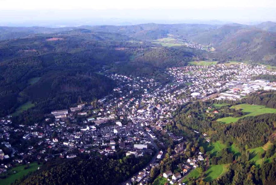 Luftaufnahme von Bad Laasphe. Die Stadt von oben, gesäumt von mittelgebirgigen Anhöhen und Wald.
