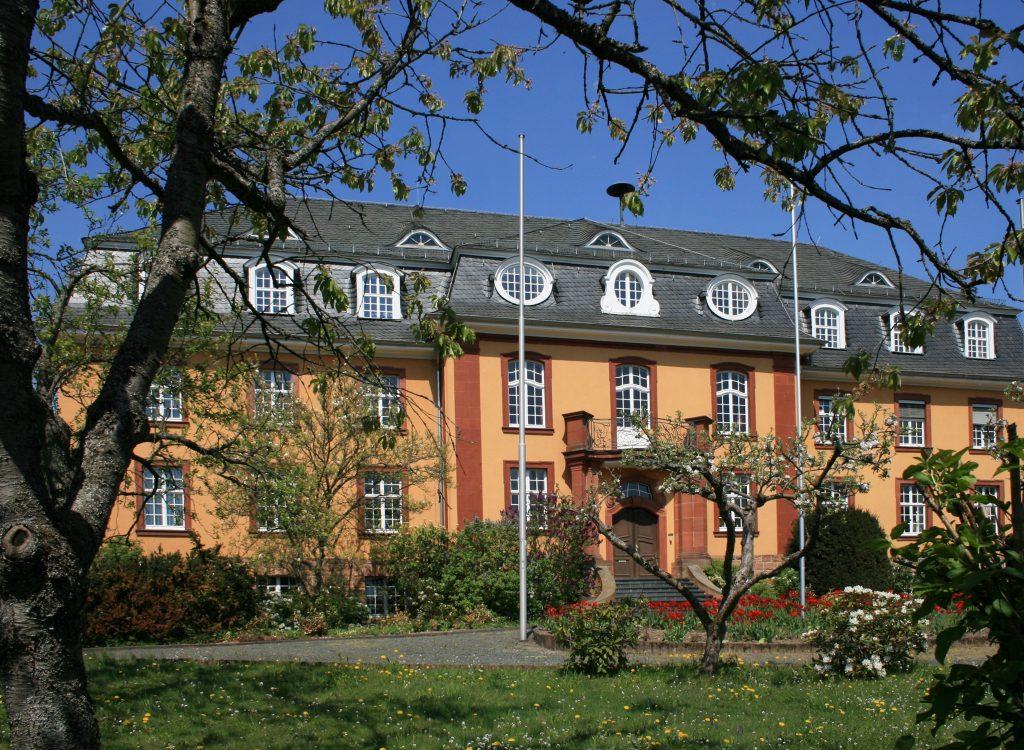 Das Landratsamt (Front) mit Erker und Gauben. In Biedenkopf. Im Frühling. Blühende Bäume im Vordergrund.