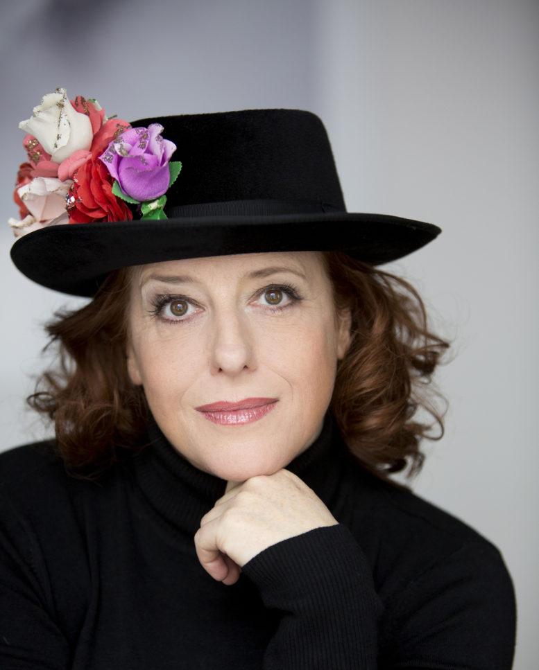 Die aus dem Fernsehen bekannte Kabarettistin Luise Kinseher ist auf diesem Porträtfoto zu sehen - mit blumendekoriertem Hut und schwarzem Pulli.