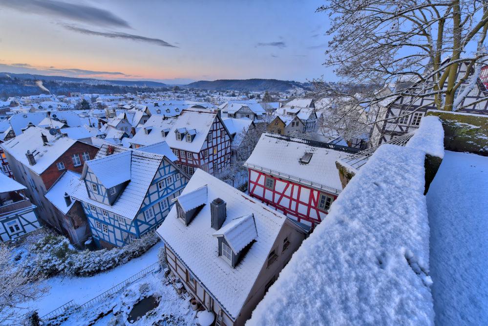 Blick über die Dächer von Marburg. Schneebedeckt im Morgengrauen.