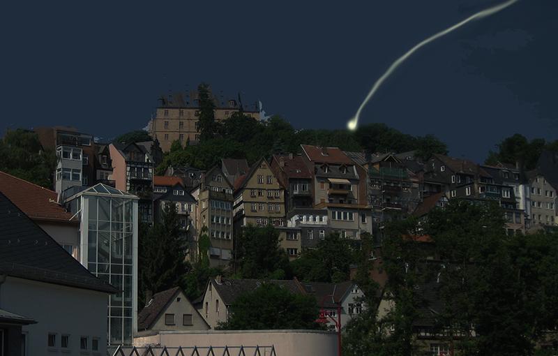 Marburg bei Nacht. Oben das Schloss, darunter Häuser. Ein Lichtpunkt mit Lichtspur ist am Himmel zu sehen.