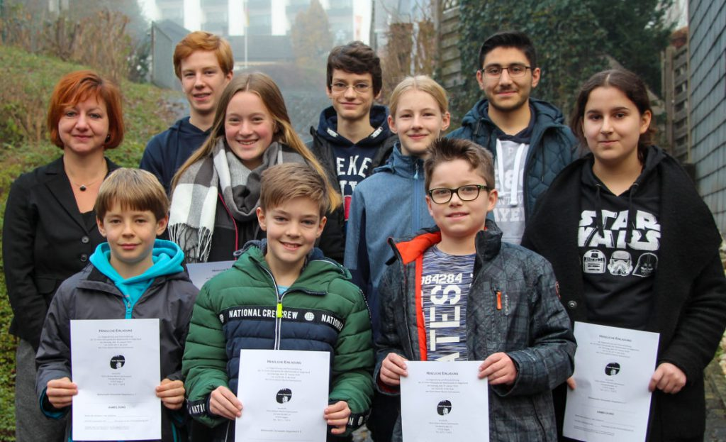 9 Schüler'innen und Lehrerin mit Urkunden in drei Reihen zum Gruppenfoto aufgestellt.