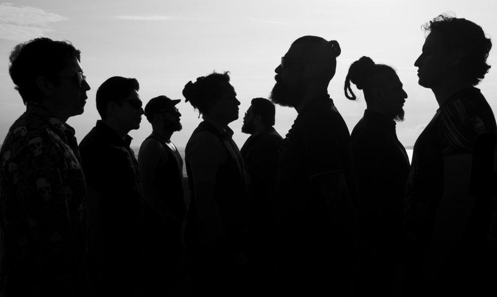 Nur die Silhouetten der 8 Musiker sind zu sehen - im Profil. Schwarz. Auf hellem Hintergrund.