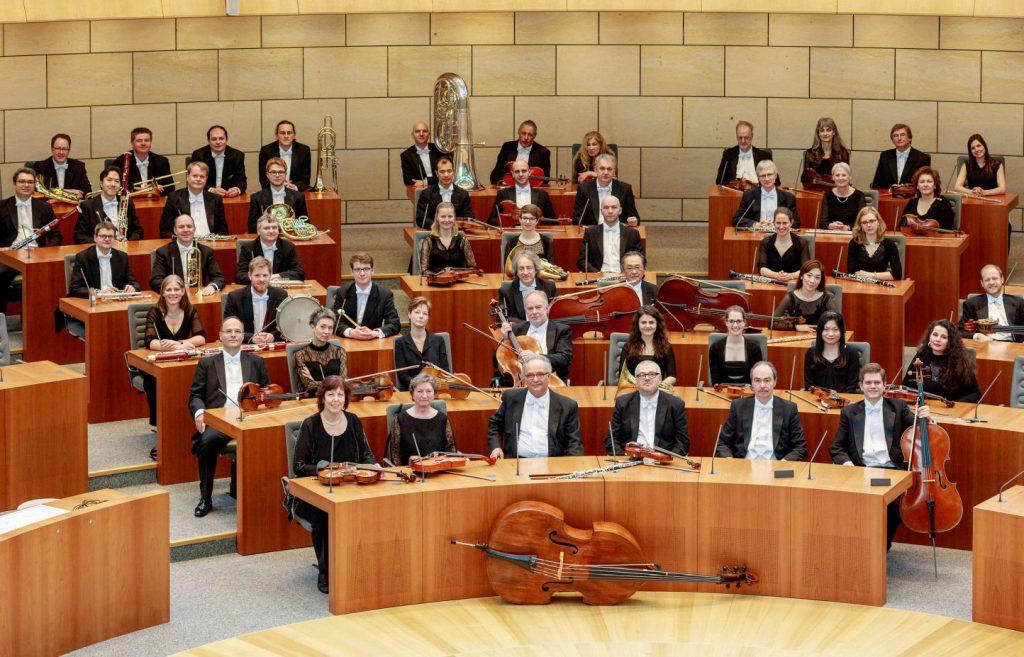 Die Musikerinnen und Musiker der Philharmonie mit ihren Instrumenten. Sitzend, aber nicht spielend.