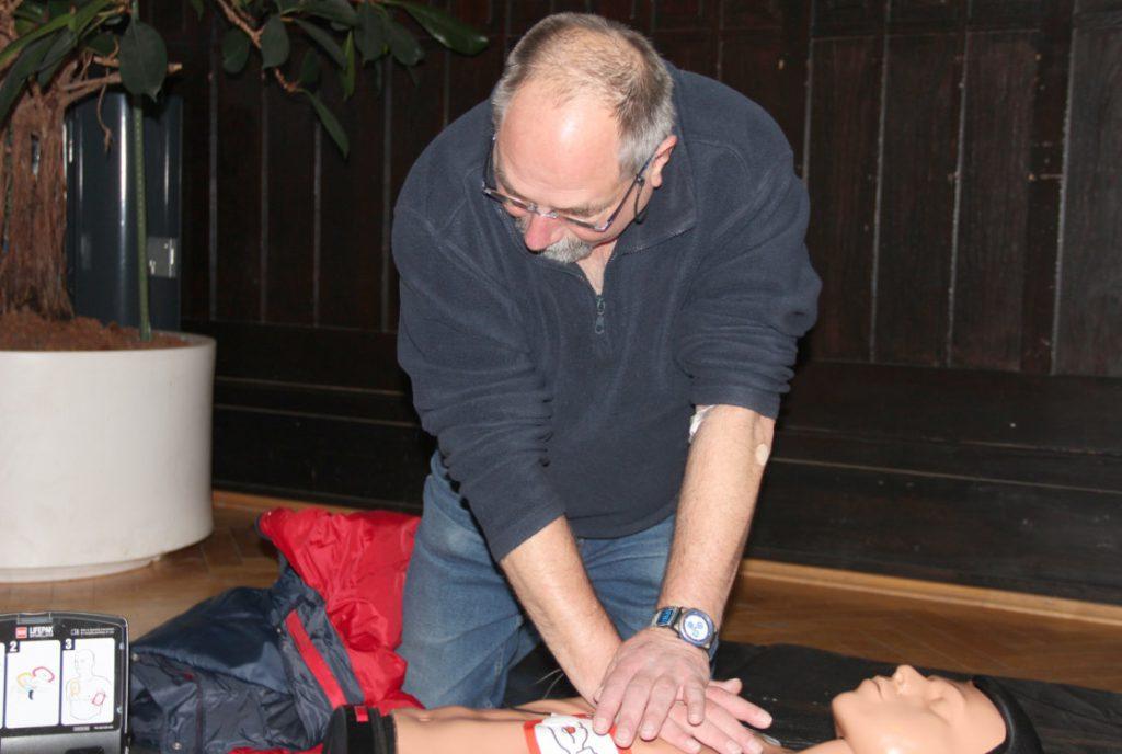 Ein Mann zeigt wie die Herz-Lungen-Wiederbelebung ausgeführt wird mit Hilfe eines Defibrillators an einer Übungspuppe.