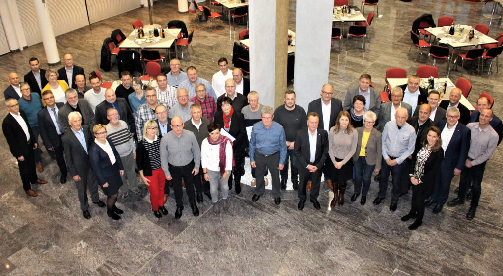 Gruppenfoto mit Arbeitsjubilaren, Rentnern und Vorstandsmitgliedern im Roth-Atrium. Im Hintergrund gedeckte Tische.