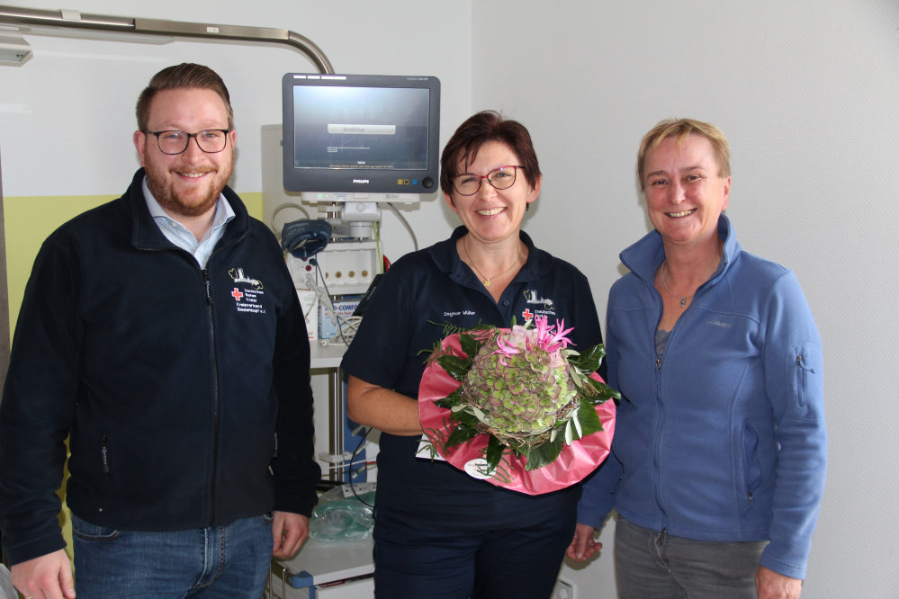 Drei Mitarbeiter des DRK in einem Krankenzimmer mit Überwachungsmonitor, in der Mitte mit Blumenstrauß die neue Atemtherapeutin.