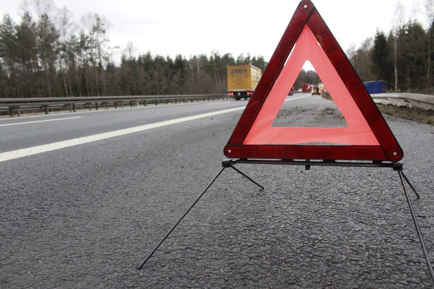 Am Rand der Autobahnauffahrt steht ein rotes Warndreieck. Im Hintergrund einzelne Fahrzeuge.
