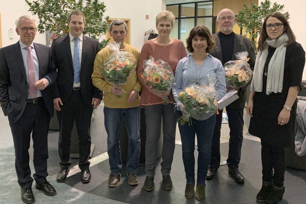 Die Gewinnerinnen und Gewinner mit jeweils einem Blumenstrauß stellen sich zum Gruppenfoto mit den Bankangestellten.