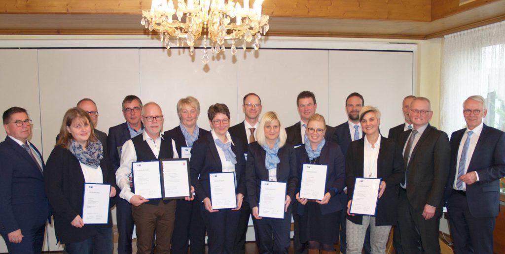 16 schick gekleidete Männer und Frauen. Arbeitsjubilare der VR Bank und Vorstandsmitglieder. Festlich aufgestellt zum Gruppenfoto.