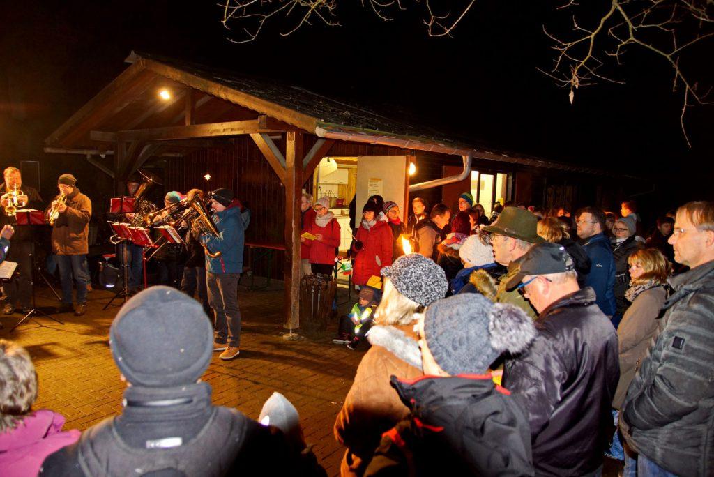 Die beleuchtete Schutzhütte. Davor viele winterlich gekleidete Menschen die dem Posaunenchor zuhören.