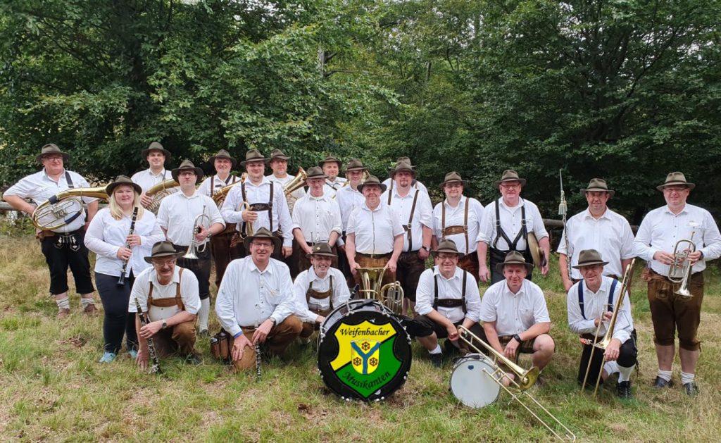 Die Weifenbacher Musikanten - alle im weißen Hemd, mit Lederhosen und Hüten und mit Instrument hocken und stehen als Gruppe auf der Wiese.