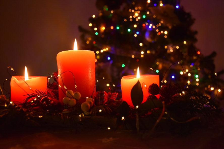 Drei brennende, rote Kerzen. Im Hintergrund ein Weihnachtsbaum zu erahnen. Bunte Lichter daran.