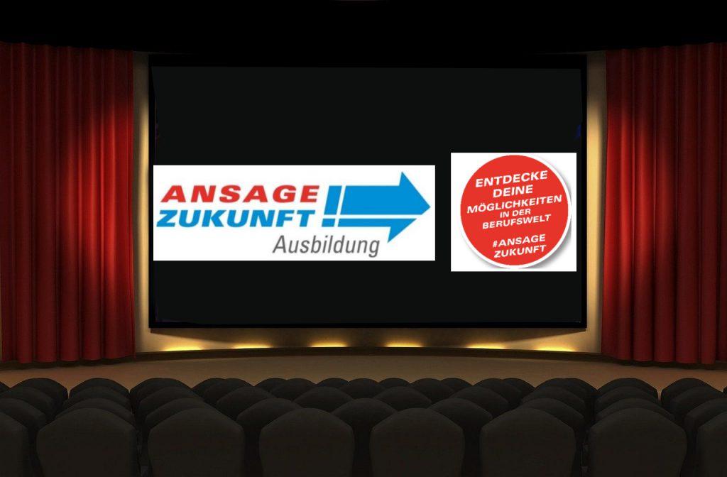 Eine Kinoleinwand mit dem Logo der Veranstaltung. Einige leere Stuhlreihen davor - rechts und links der Vorhang.
