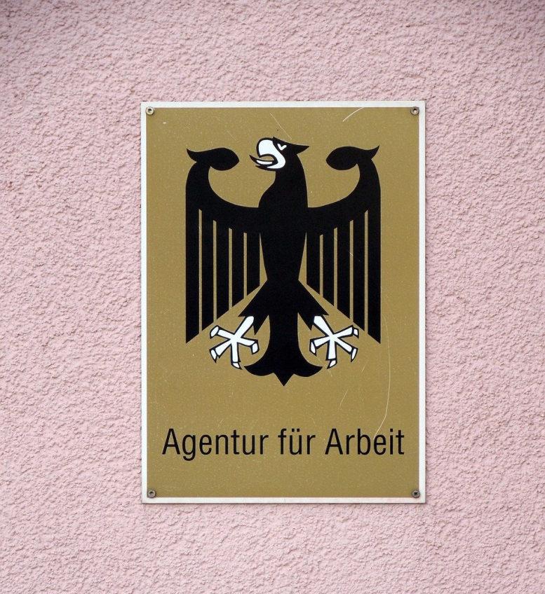 Schild mit Logo (Bundesadler) der Agentur für Arbeit auf rosa Putz-Untergrund.