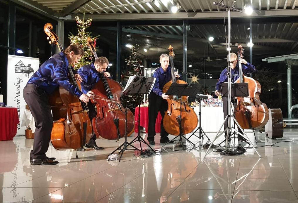 """Die vier Kontrabassisten """"The Flying Bassis"""" mit ihren Kontrabässen und einheitlich gekleidet (blaues Hemd, schwarze Hose) geben einen akustischen Einblick in ihr Repertoire."""