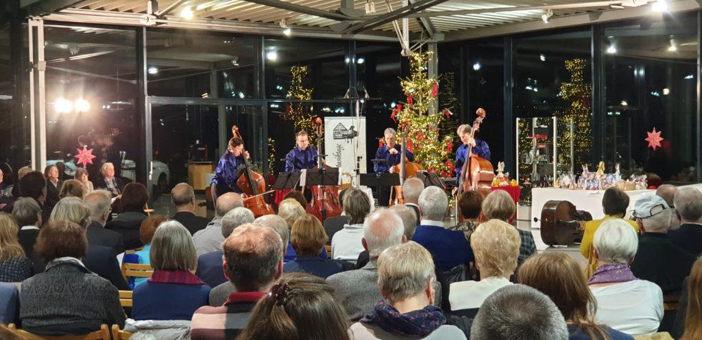 Die vier Bassisten beim Auftritt im Glaspavillon, das Publikum im fast vollbesetzten Saal lauscht konzentriert. Der Pavillon ist mit Weihnachtsbaum und -deko adventlich geschmückt.