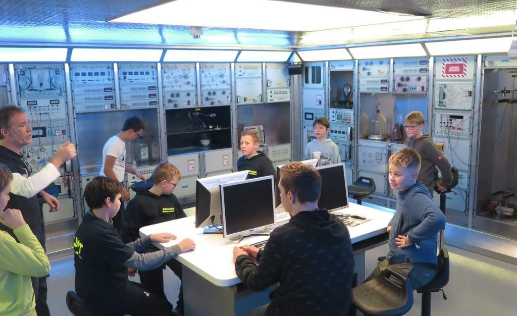 Die Schüler des GSW sitzen an einem Tisch im Raumfahrtlabor und haben Rechner vor sich. Im Hintergrund technische Anlagen undefinierbarer Art.