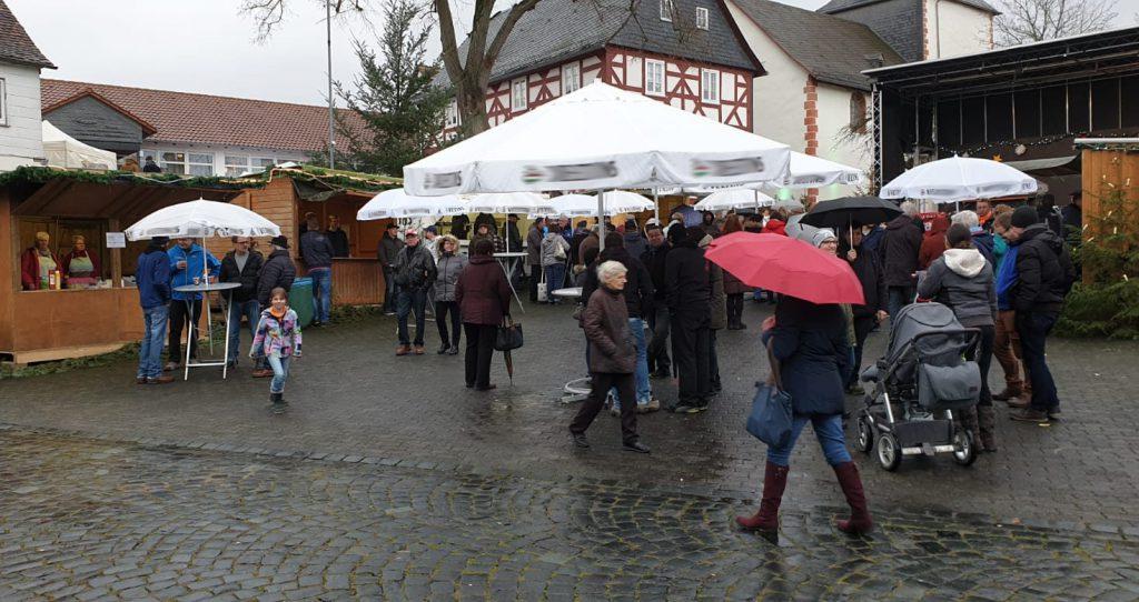Einige Besucher mit Regenschirmen schlendern über den Buchenauer Weihnachtsmarkt.