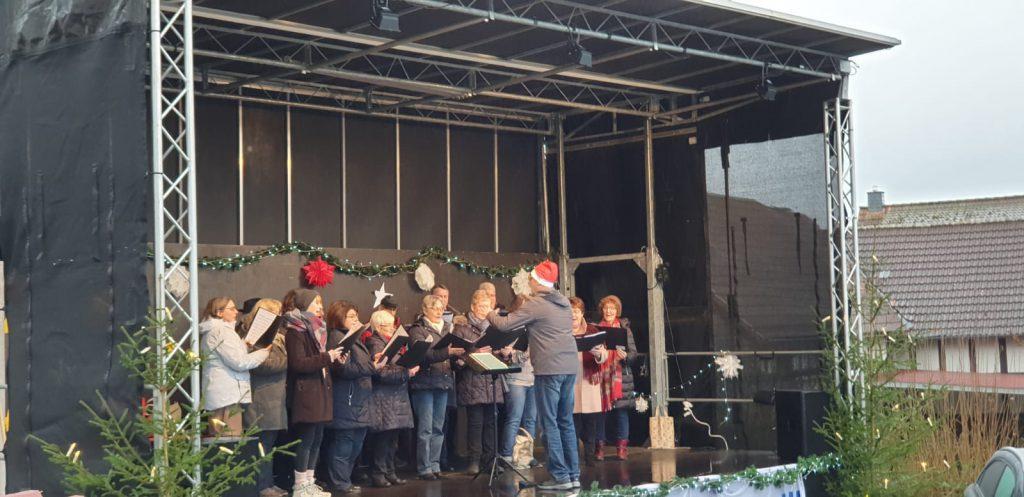 Sängerinnen singen auf der Aktionsbühne am Weihnachtsmarkt in Buchenau. Der Dirigent trägt eine Nikolausmütze.