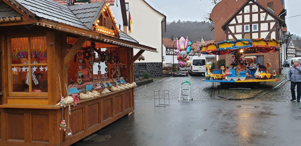 Marktbude und Karussell auf dem Weihnachtsmarkt in Buchenau. Nur 1 Besucher ist zu sehen. Es regnet.