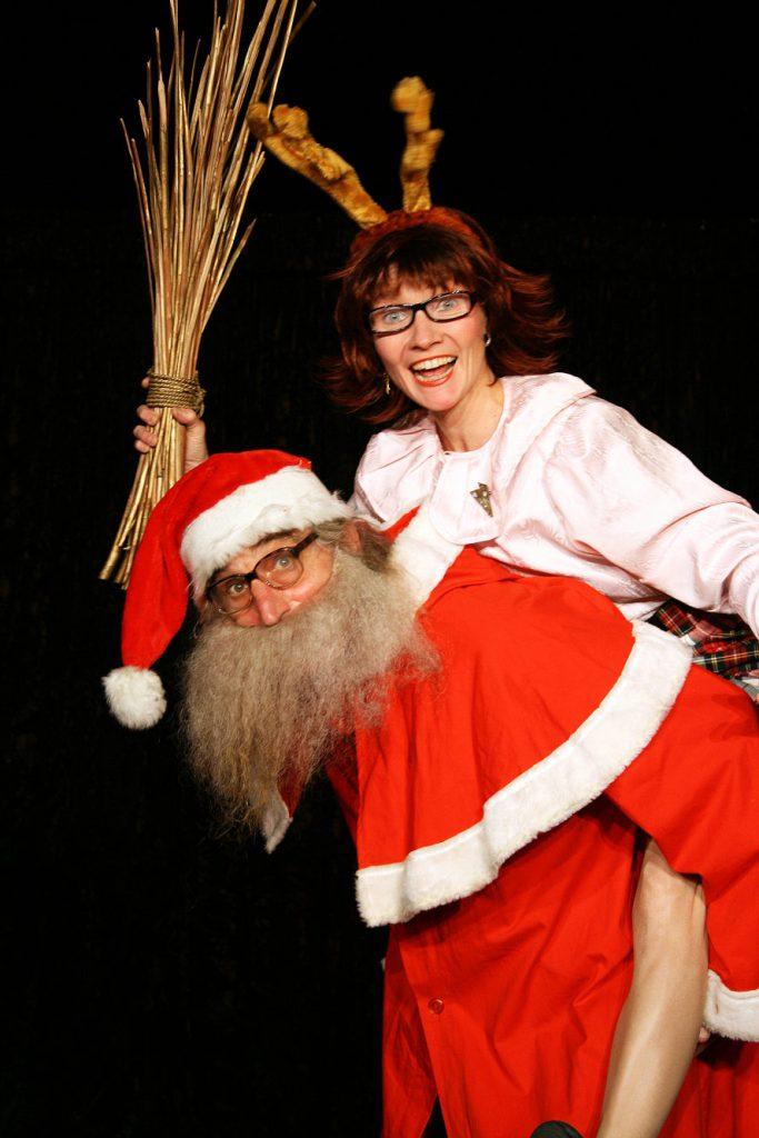 Ein Weihnachtsmann und eine als Rentier verkleidete Frau mit einer Rute in der Hand lachen in die Kamera.