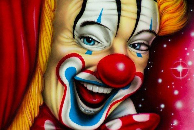 Eine farbenfrohe Grafik eines Clown-Gesichts mit roter Nase und klassisch geschminktem Gesicht.