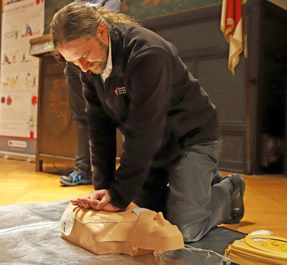 """DRK-Ausbilder Joachim Scholz zeigt an einem künstlichen Modell, wie eine Herzdruckmassage durchzuführen ist und presst seine Hände auf den """"Brustkorb""""."""