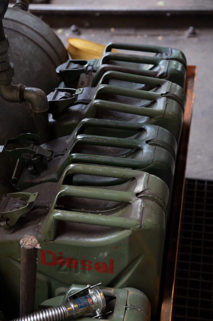 Mehrere Dieselkanister in Reih und Glied auf einem Hof stehend.