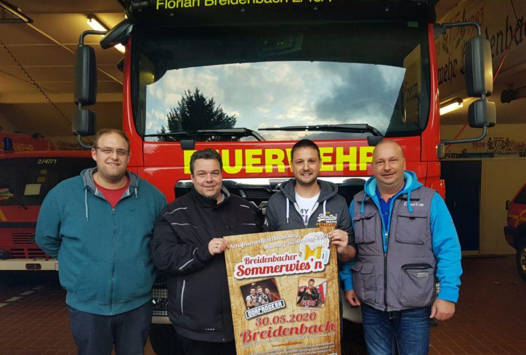4 Männer stehen vor einem Feuerwehrfahrzeug und halten das Plakat für das Sommerfest.