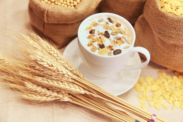 Getreide in Säcken und als Ähren und eine Tasse mit Körnermüsli.