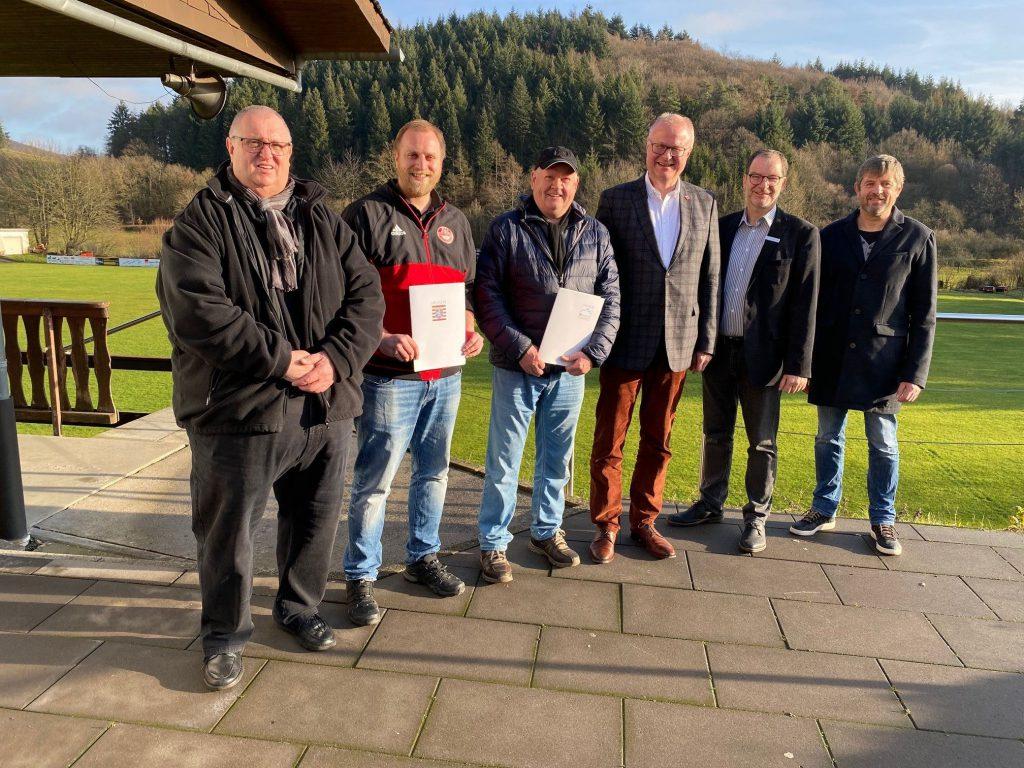 Fünf Fußballvereinsmitglieder mit Finanzminister Schäfer stehen in Reih und Glied und freuen sich über das Geld.