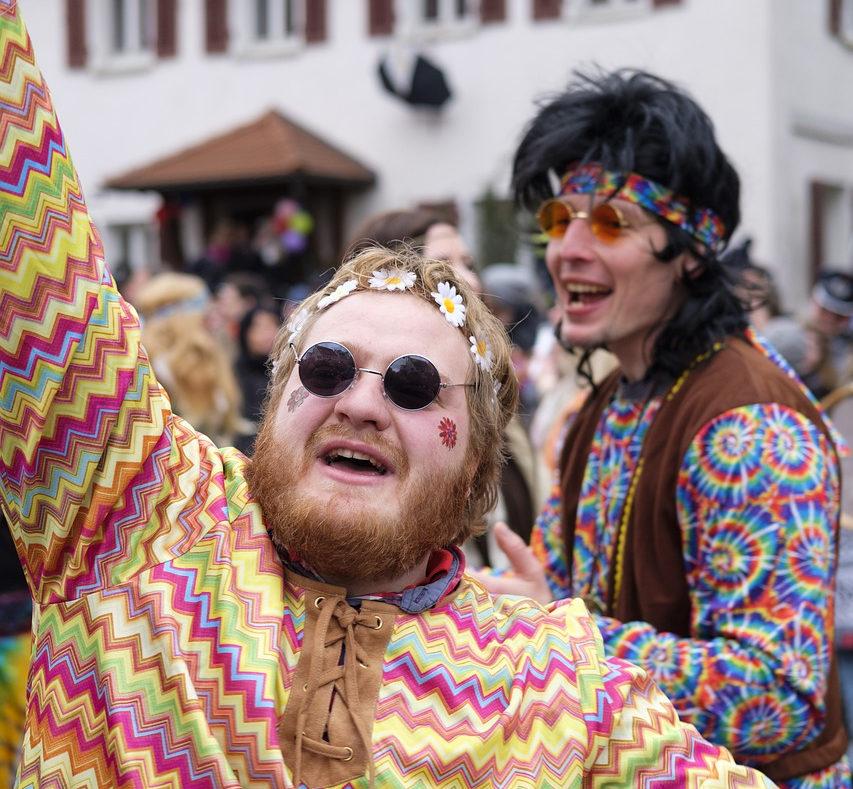 2 wie Hippies gekleidete junge Männer mit Blumenstirnband und bunten Oberteilen, tanzen ausgelassen.