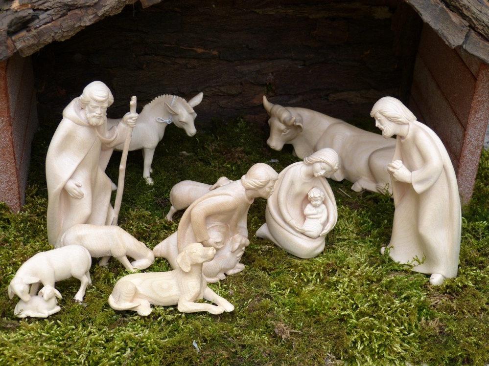 Hirten (geschnitzt) an der Krippe beim Jesuskind. Staunend. Ergriffen. Anbetend. Die Bedeutung erkennend.