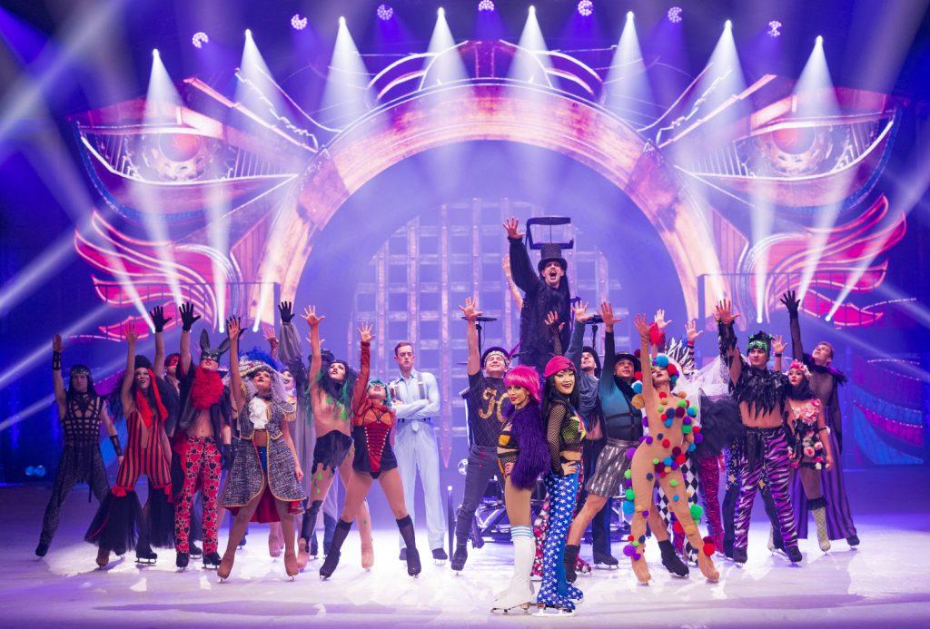 Auf der Showbühne positionieren sich zwei Dutzend kostümierte Eisläuferinnen und -läufer.