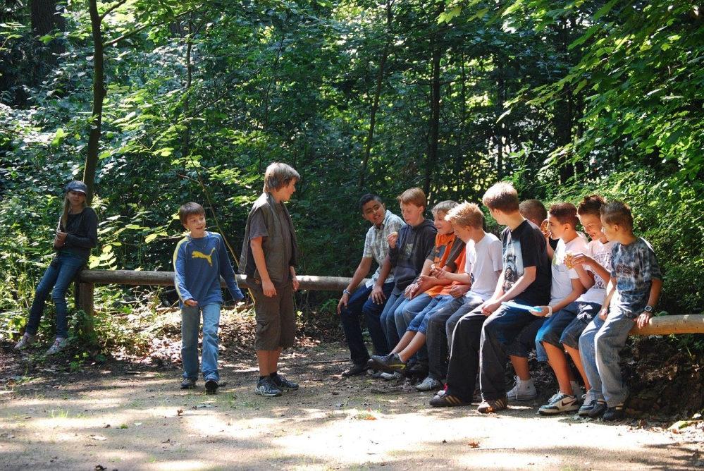 Neun Jungs im Alter zwischen 11 und 14 Jahren sitzen auf einem querliegenden Baumstamm. Zwei stehen davor, ein Mädchen lehnt an einem Baum.