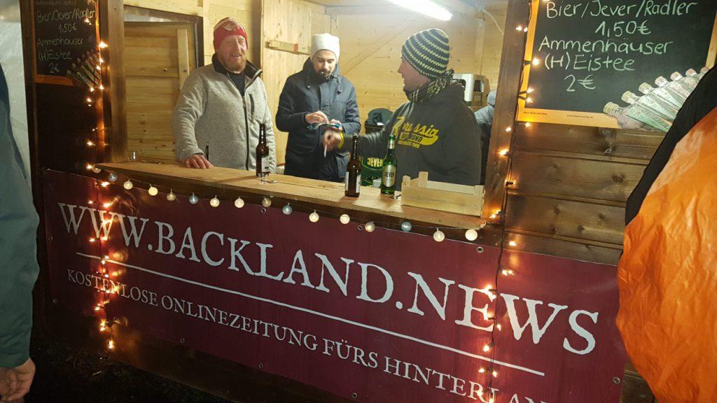 Eine Holzbude, dahinter drei bemützte Fußballvereinsmitglieder. Die Backland.News-Werbung ziert die Front der Bude.