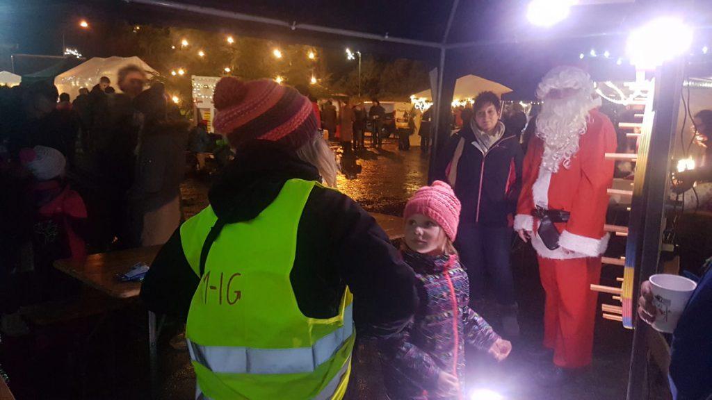 Ein Kind am Glücksrad, daneben weitere Weihnachtsmarktbesucher und der Nikolaus persönlich.