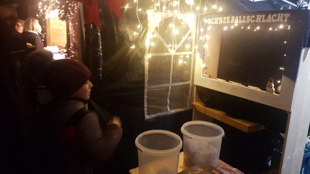 """Ein Weihnachtsmarktstand mit einer Wurfbude mit dem Titel """"Schneeballschlacht"""". Der Stand ist von Lichterketten umrahmt."""