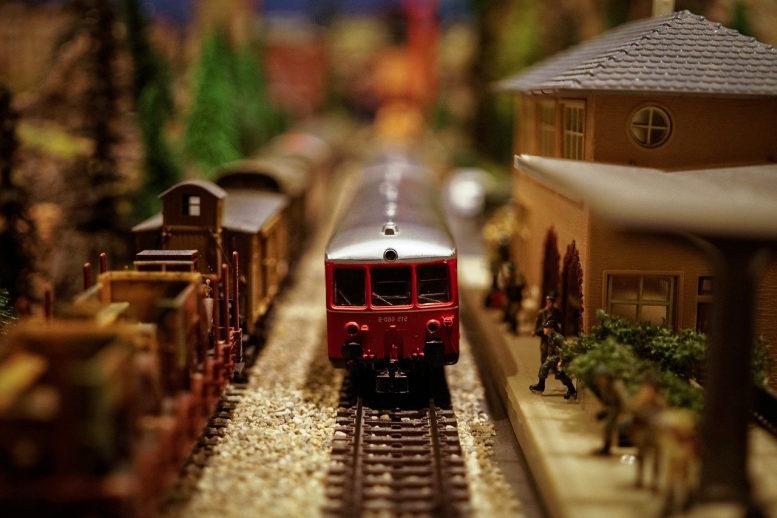 Eine Modellbahnanlage (Ausschnitt). Eine rote Lok aus den 80ern in einem Bahnhof, daneben Güterwaggons, alles im Miniformat.