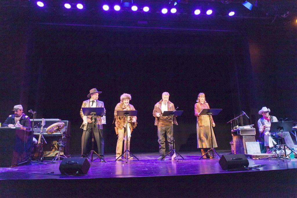 6 Als Cowboy (1 Cowgirl ist dabei) verkleidete Sprecher und Geräusch-Erzeuger stehen miteinander auf der Bühne vor ihren Skripten.