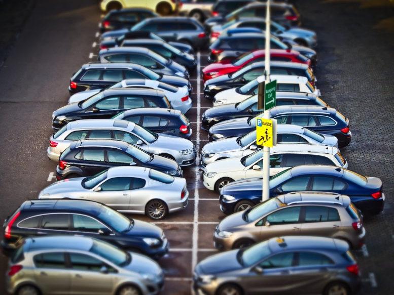 Zwei Reihen Autos stehen parkend auf einem Parkplatz.
