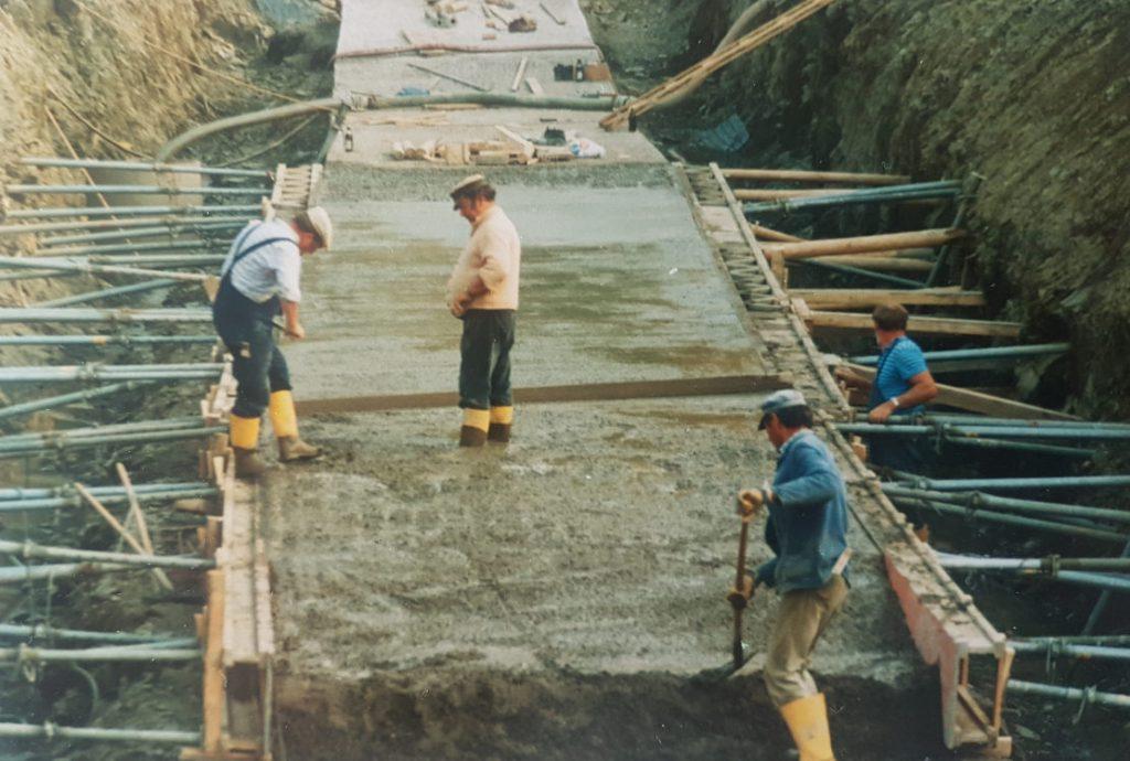 Arbeiter (4 Personen= bringen den Beton ein.