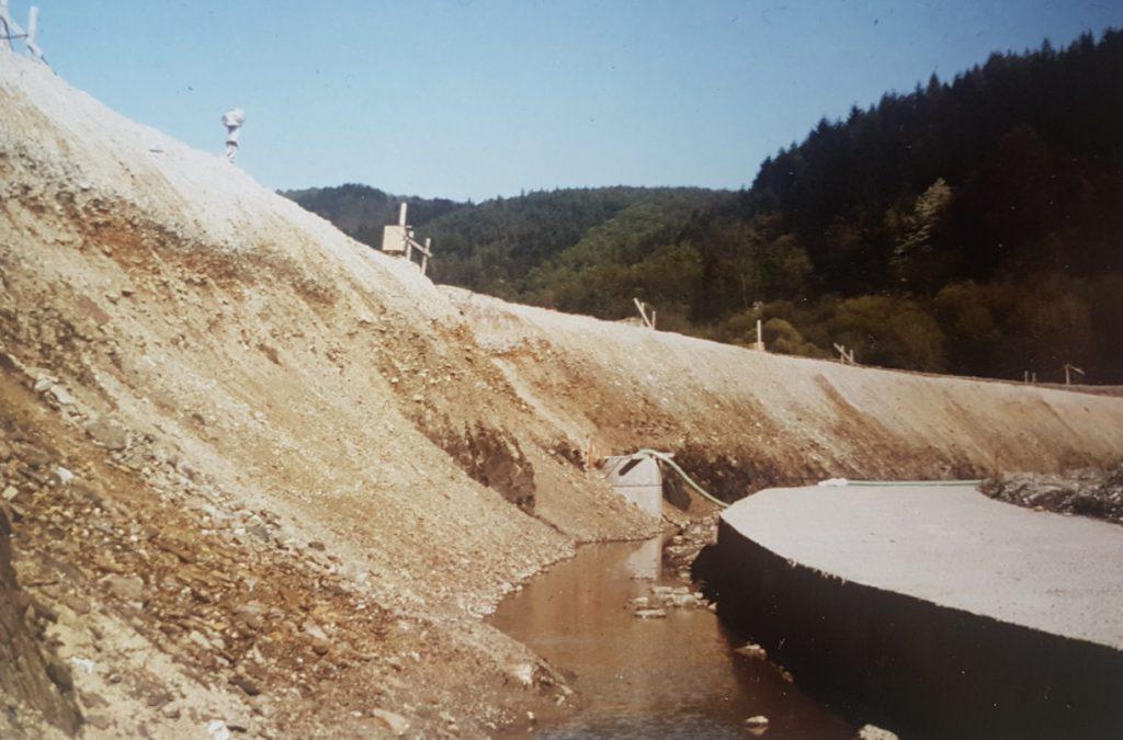 Historischer Blick zum Bau des Hochwasserrückhaltebeckens- hier  ein Blick von unten auf die Dammkrone. Alles noch Erde.