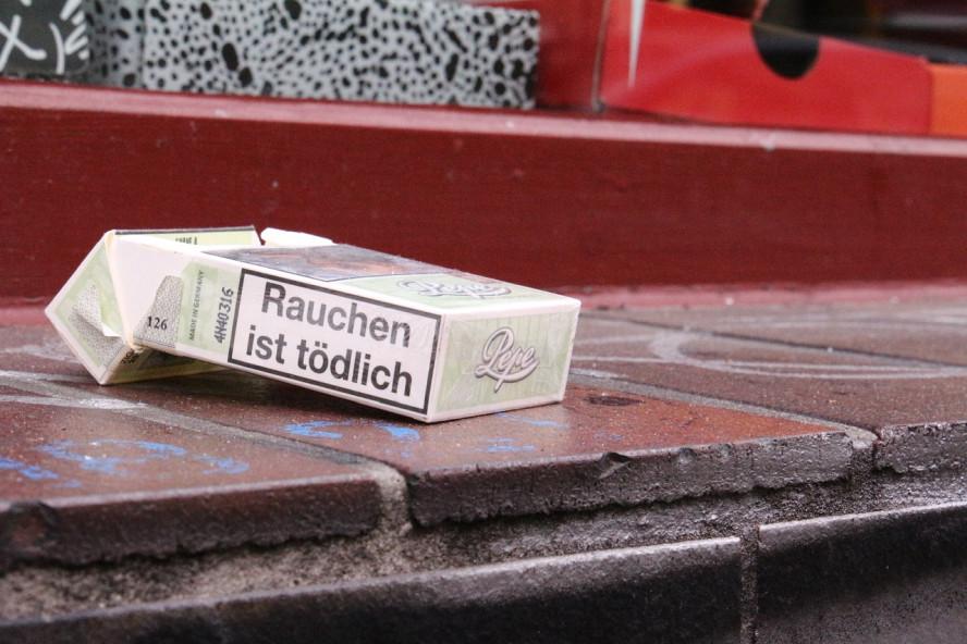 """Eine angebrochene Zigarettenschachtel liegt verlassen auf einer Außenfensterbank. Die Aufschrift auf der Banderole: """"Rauchen ist tödlich""""."""