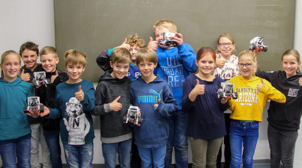 Schüler (ca. 10 Jahre alt) halten ihre Roboter ins Bild und freuen sich.